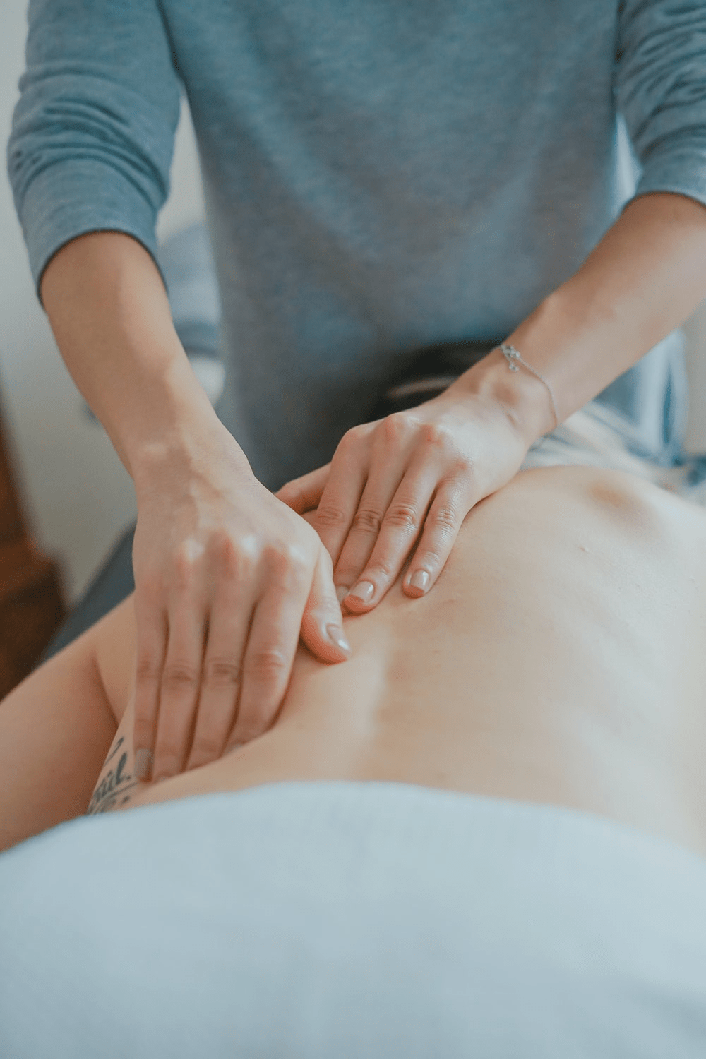 Masseuse working on a person's back